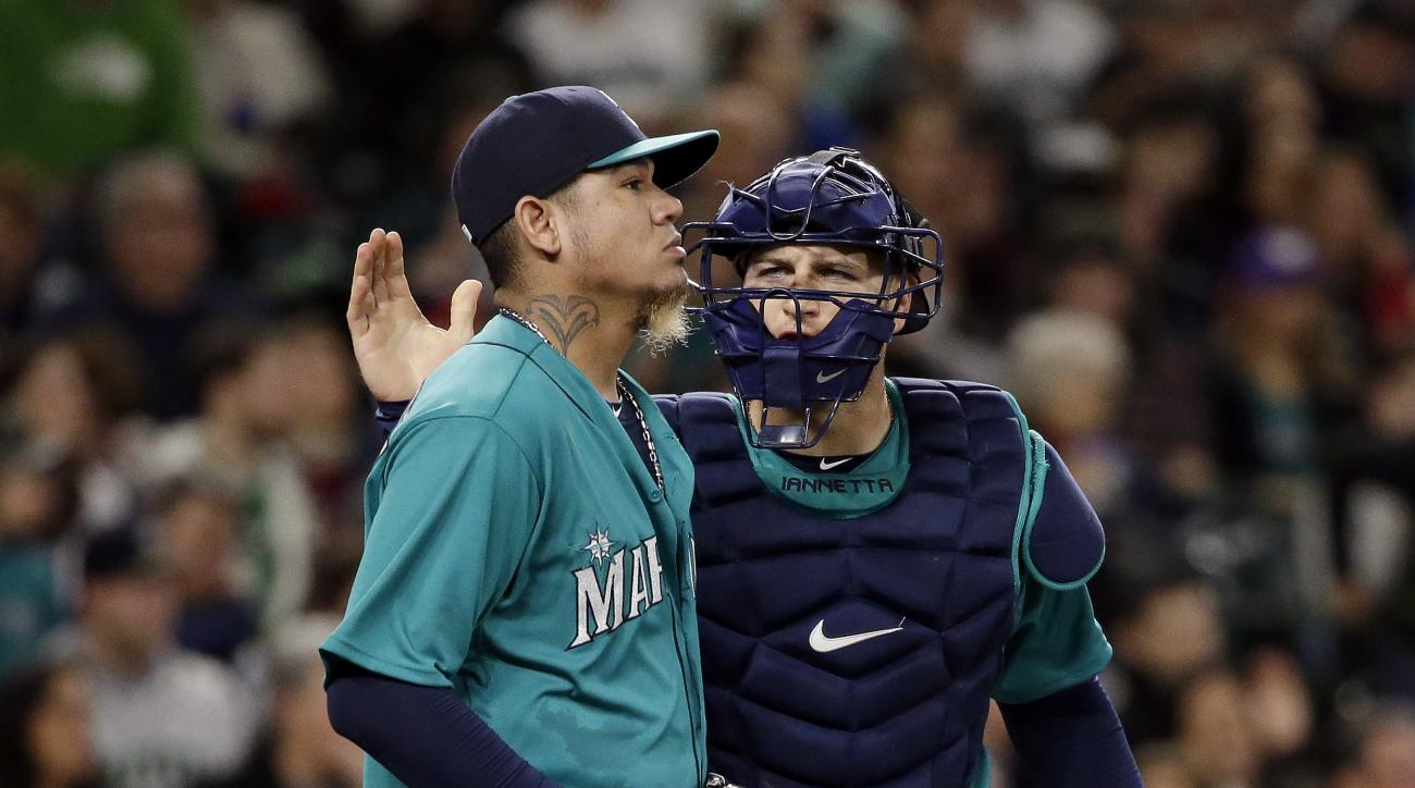 Seattle Mariners catcher Chris Iannetta, right, gives a pat to starting pitcher Felix Hernandez after a play during the third inning of a baseball game against the Minnesota Twins on Friday, May 27, 2016, in Seattle. Hernandez gave up five runs in the inn