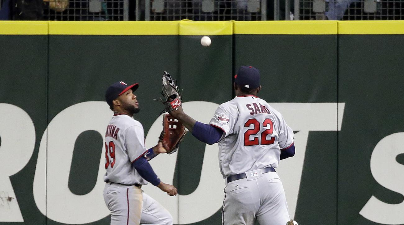 A fly ball falls between Minnesota Twins center fielder Danny Santana and right fielder Miguel Sano (22) for a triple by Seattle Mariners' Robinson Cano during the fourth inning of a baseball game Friday, May 27, 2016, in Seattle. (AP Photo/Elaine Thompso