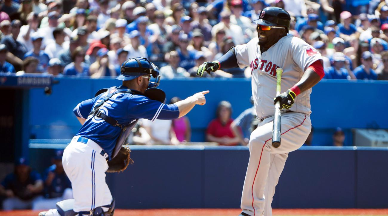 Boston Red Sox designated hitter David Ortiz (34) reacts after apparently taking a foul ball to his leg as Toronto Blue Jays catcher Russell Martin (55) looks on during the fifth inning of baseball game in Toronto, Saturday, May 28, 2016. (Nathan Denette/