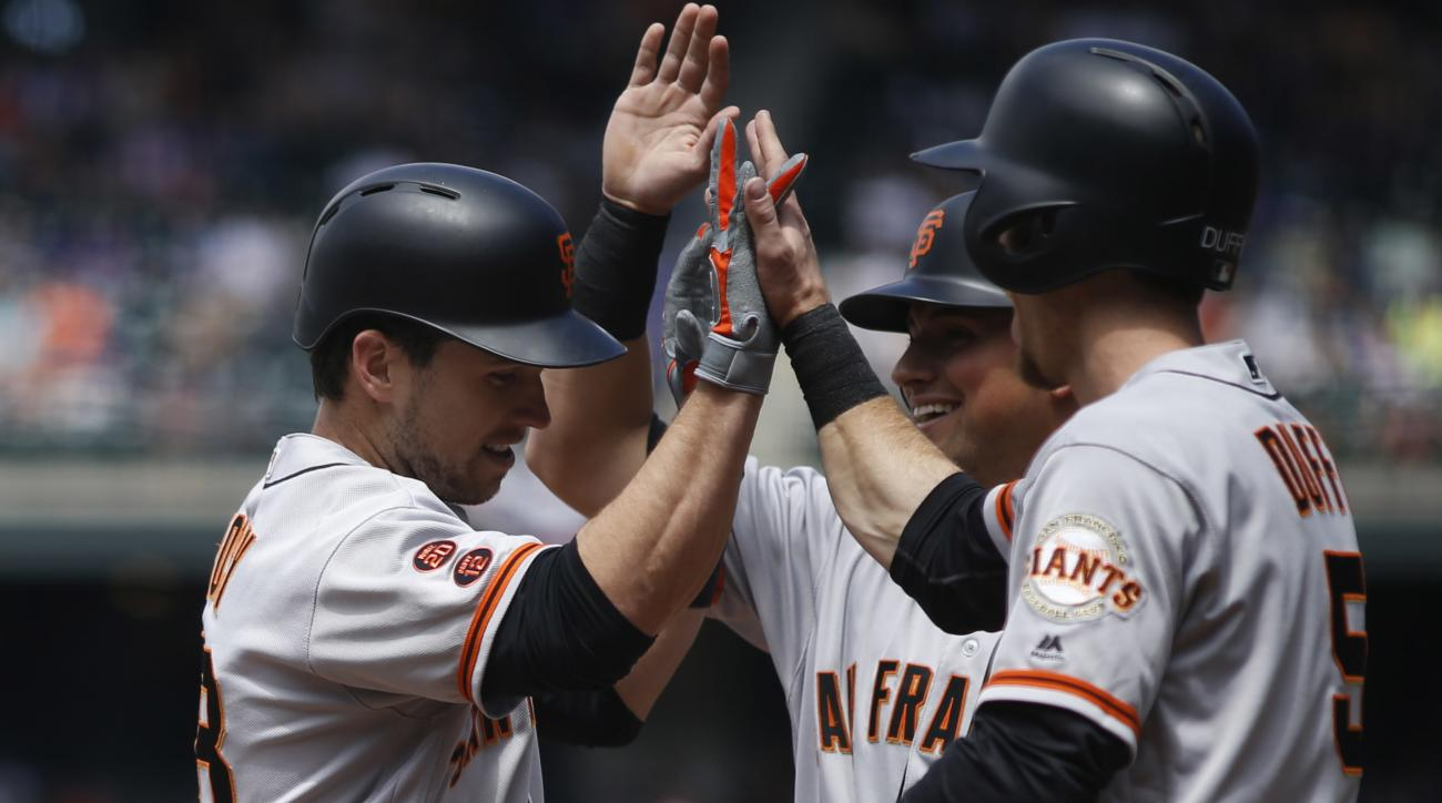 San Francisco Giants' Buster Posey, left, is congratulated by Gregor Blanco, back right, and Matt Duffy after hitting a three-run home run off Colorado Rockies starting pitcher Eddie Butler in the first inning of a baseball game Satuday, May 28, 2016, in