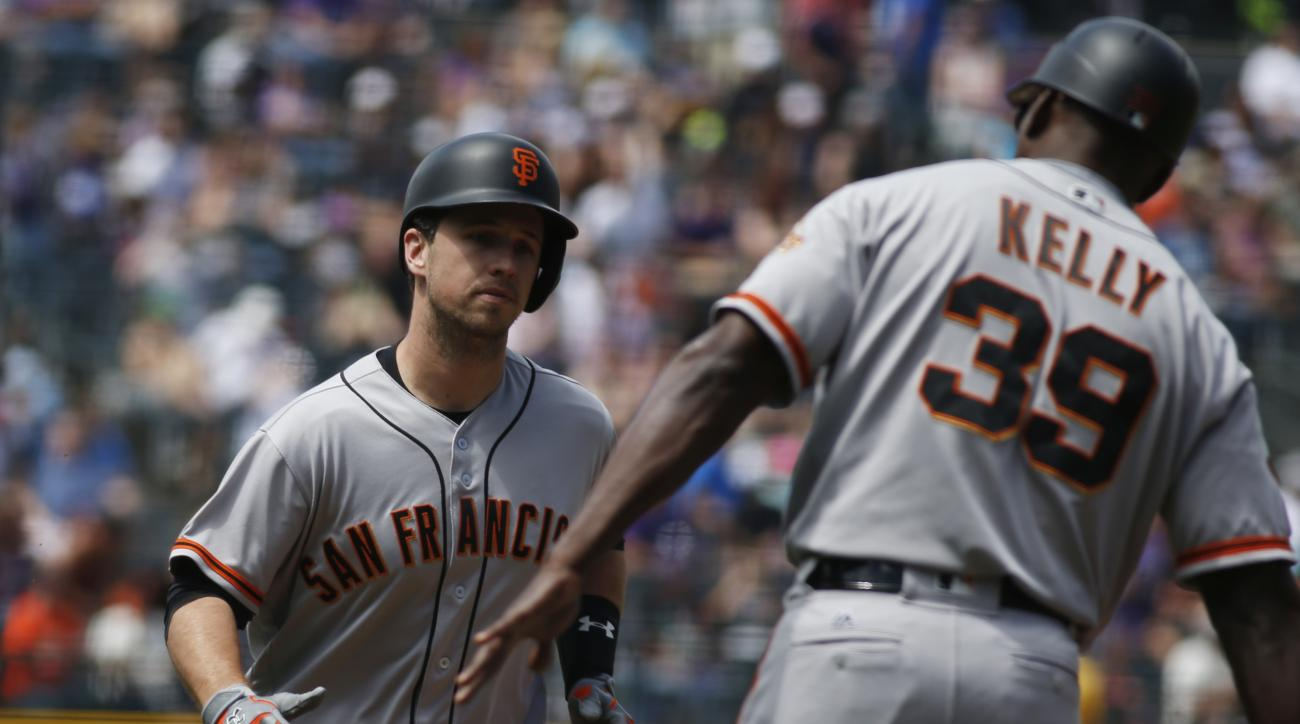 San Francisco Giants' Buster Posey, left, is congratulated by third base coach Roberto Kelly while rounding third base after hitting a three-run home run off Colorado Rockies starting pitcher Eddie Butler in the first inning of a baseball game Saturday, M