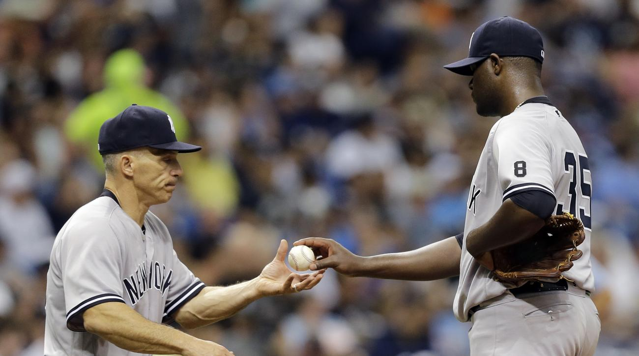 New York Yankees starting pitcher Michael Pineda, right, hands the baseball to manager Joe Girardi as he is taken out of the game against the Tampa Bay Rays during the fourth inning of a baseball game, Saturday, May 28, 2016, in St. Petersburg, Fla. (AP P
