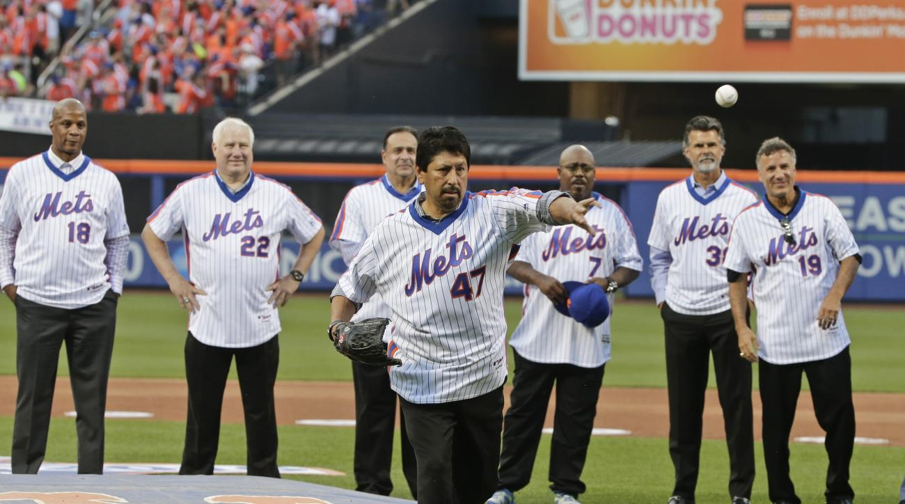 Former New York Mets pitcher Jesse Orosco (47) throws a ceremonial first pitch before a baseball game between the Los Angeles Dodgers and the Mets as his teammates watch Saturday, May 28, 2016, in New York. (AP Photo/Frank Franklin II)
