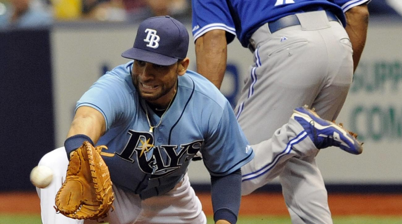 FILE - In this Oct. 4, 2015, file photo, Tampa Bay Rays first baseman James Loney reaches for the late throw as Toronto Blue Jays' Ben Revere is safe with an infield base hit during the first inning of a baseball game in St. Petersburg, Fla. The New York