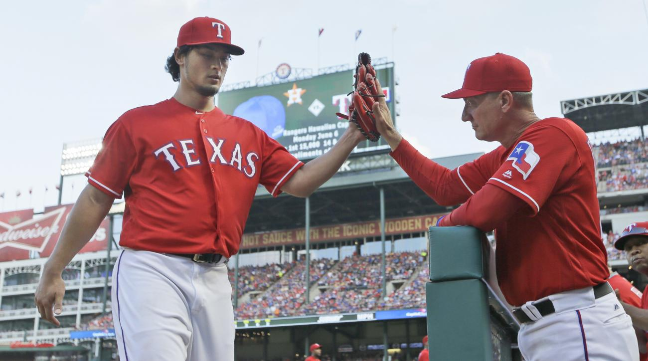 Texas Rangers starting pitcher Yu Darvish, left, of Japan, is congratulated by manager Jeff Banister while coming off the field during the third inning of a baseball game against the Pittsburgh Pirates in Arlington, Texas, Saturday, May 28, 2016. (AP Phot
