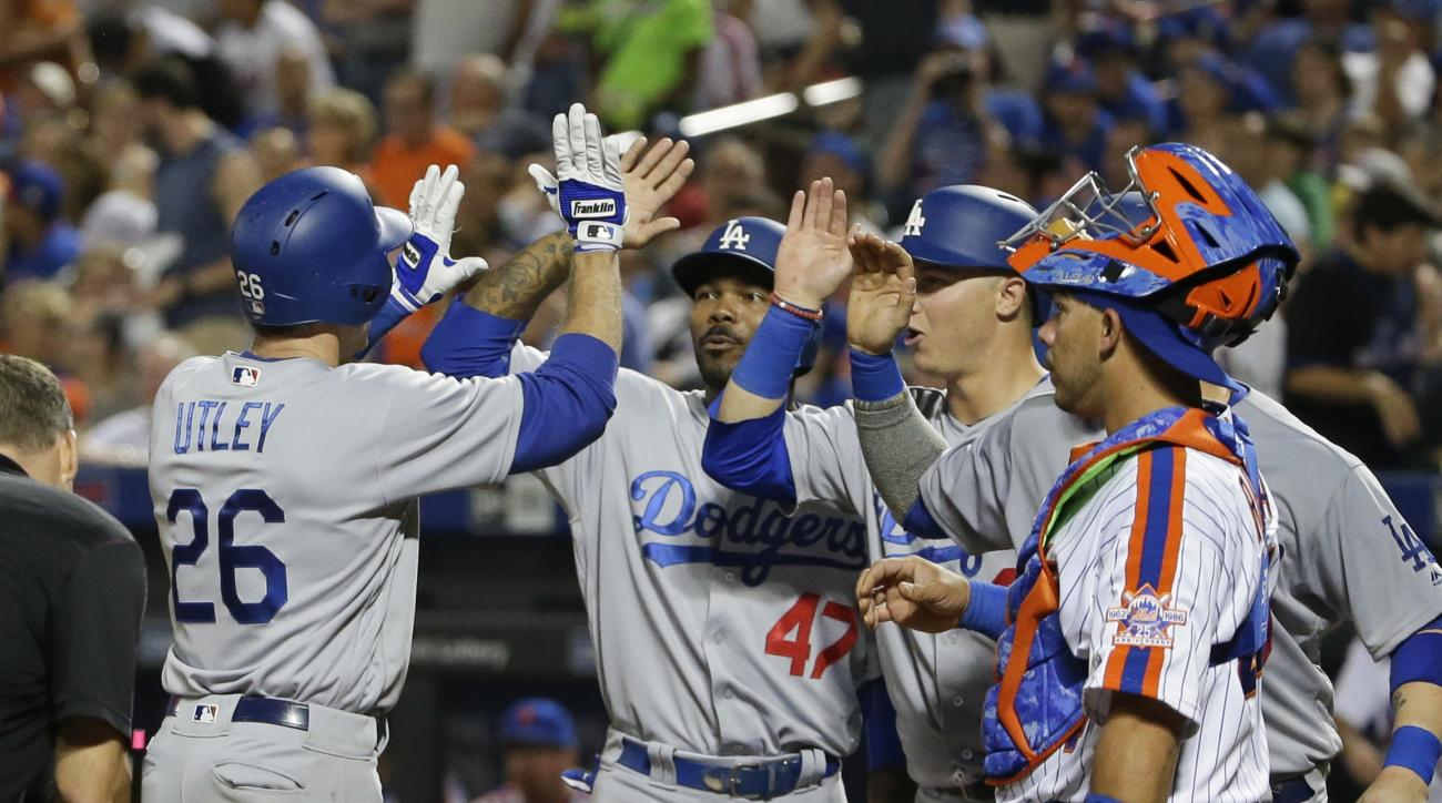 New York Mets catcher Rene Rivera (44) watches as Los Angeles Dodgers' Chase Utley (26) celebrates with teammates after hitting a grand slam home run during the seventh inning of a baseball game, Saturday, May 28, 2016, in New York. (AP Photo/Frank Frankl