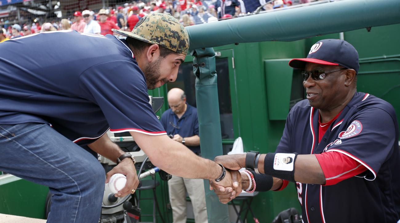 "Medal of Honor recipient retired U.S. Army Capt. Florent ""Flo"" Groberg, left, is greeted by Washington Nationals manager Dusty Baker before a baseball game between the Nationals and the St. Louis Cardinals at Nationals Park, Sunday, May 29, 2016, in Washi"