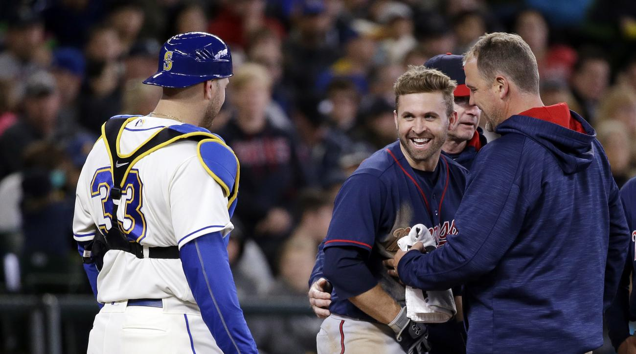 Minnesota Twins' Brian Dozier smiles as he looks across at Seattle Mariners catcher Chris Iannetta (33) as Dozier is checked after being hit by a pitch in the fifth inning of a baseball game, Sunday, May 29, 2016, in Seattle. Dozier remained in the game.