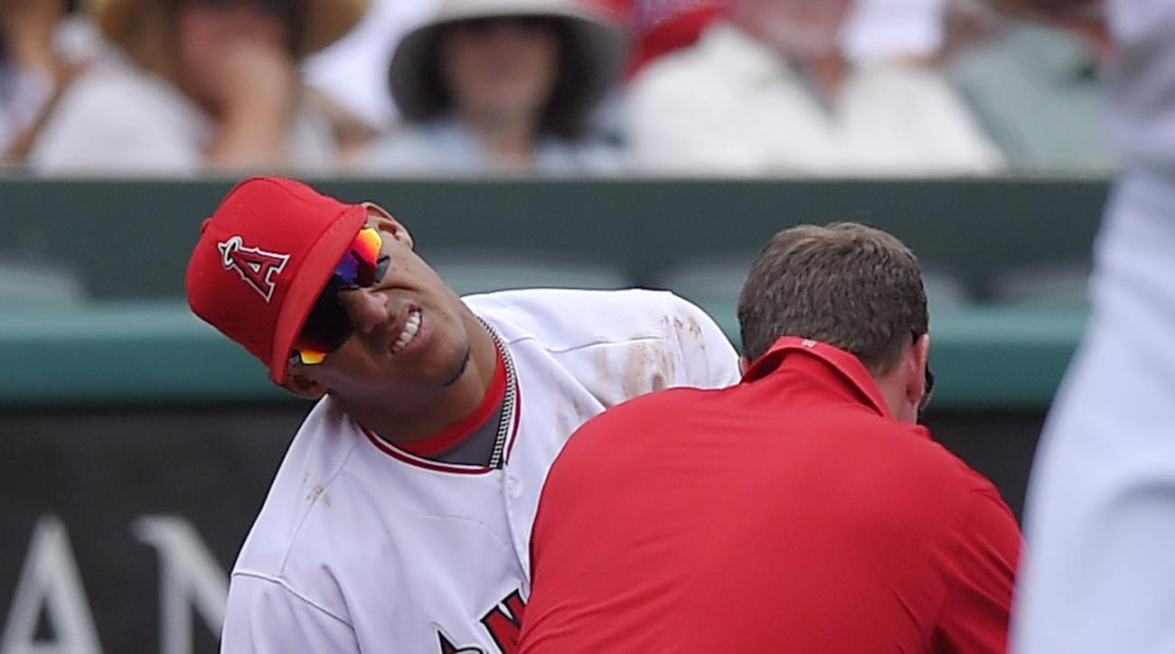 Los Angeles Angels third baseman Yunel Escobar has his left hand looked at by a trainer after injuring it while trying to field a ball by Houston Astros' Jake Marisnick during the third inning of a baseball game, Sunday, May 29, 2016, in Anaheim, Calif. E