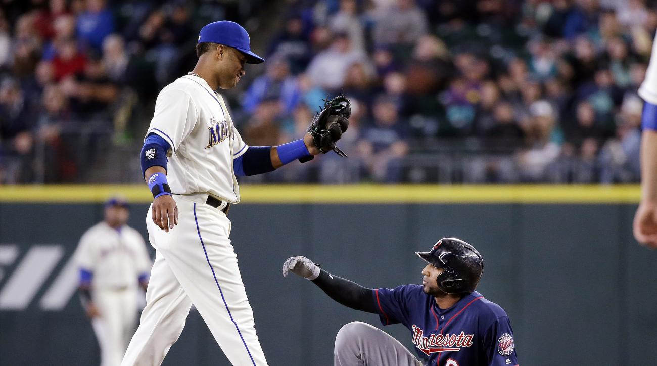 Minnesota Twins' Eduardo Nunez (9) sits and waits for Seattle Mariners second baseman Robinson Cano to tag him after Nunez slipped and fell after attempting to steal second base in the seventh inning of a baseball game Sunday, May 29, 2016, in Seattle. (A