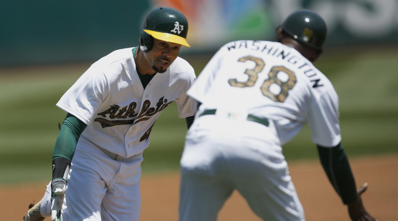 Oakland Athletics Coco Crisp, left, is congratulated by third base coach Ron Washington (38) as he rounds the bases after hitting a home run against Minnesota Twins in the first inning of a baseball game Monday, May 30, 2016, in Oakland, Calif. (AP Photo/