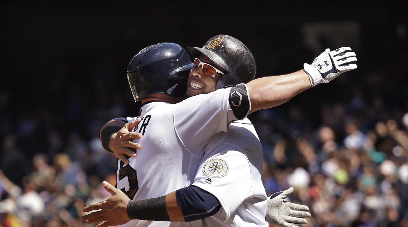 Seattle Mariners' Kyle Seager, left, is greeted at home by Nelson Cruz on Seager's two-run home run against the San Diego Padres in the sixth inning of a baseball game Monday, May 30, 2016, in Seattle. (AP Photo/Elaine Thompson)