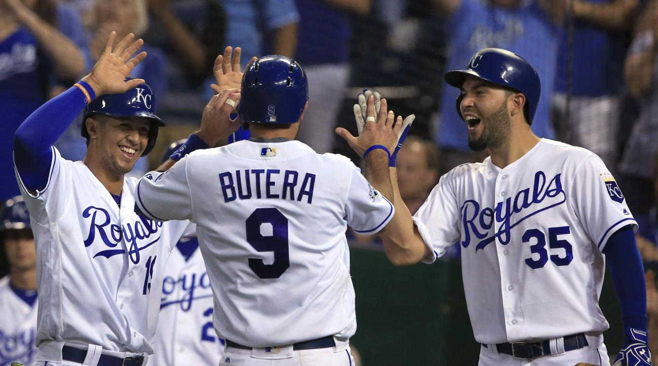 Kansas City Royals' Drew Butera (9) is welcomed home by teammates Cheslor Cuthbert, left, and Eric Hosmer (35) during the fourth inning of a baseball game against the Tampa Bay Rays at Kauffman Stadium in Kansas City, Mo., Tuesday, May 31, 2016. Butera an