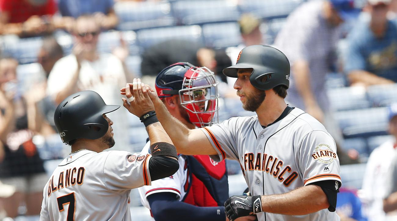 San Francisco Giants starting pitcher Madison Bumgarner, right, celebrates with Gregor Blanco (7) after hitting a two-run home run as Atlanta Braves catcher Tyler Flowers  looks on in the background in the fifth inning of a baseball game Thursday, June 2,