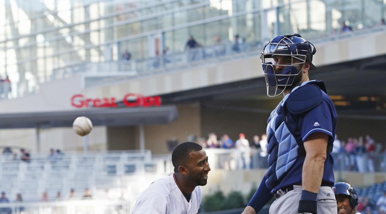 Minnesota Twins' Eduardo Nunez smiles after he scored on an inside-the-park home run off Tampa Bay Rays pitcher Matt Moore during the first inning of a baseball game Thursday, June 2, 2016, in Minneapolis. At right is Rays catcher Curt Casali. (AP Photo/J