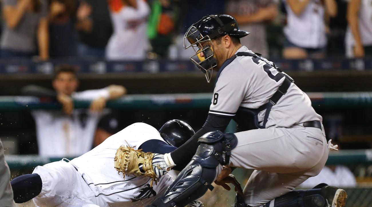New York Yankees catcher Austin Romine tags Detroit Tigers' Justin Upton out at home plate on an Ian Kinsler double during the eighth inning of a baseball game in Detroit, Thursday, June 2, 2016. (AP Photo/Paul Sancya)