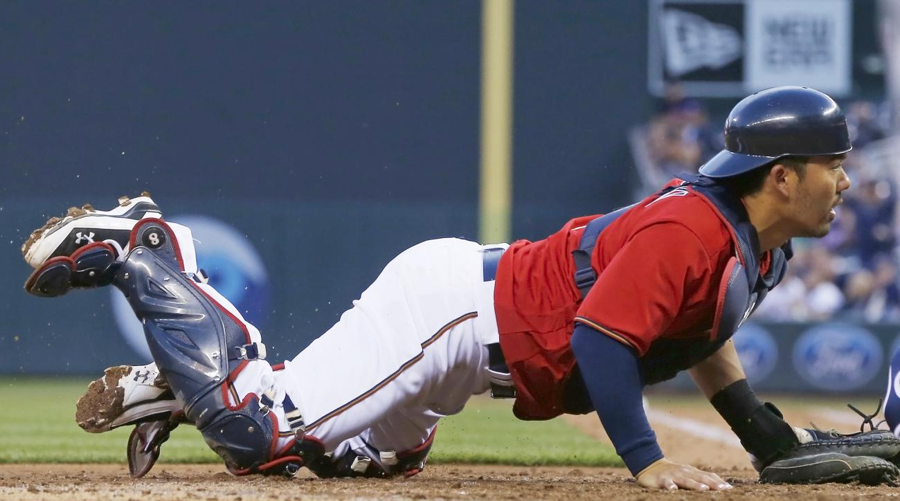 Minnesota Twins catcher Kurt Suzuki looks on as Tampa Bay Rays' Steven Souza Jr. beats Suzuki's tag to score on a sacrifice fly by Mike Mahtook, evening the score in the fifth inning of a baseball game Friday, June 3, 2016, in Minneapolis. (AP Photo/Jim M