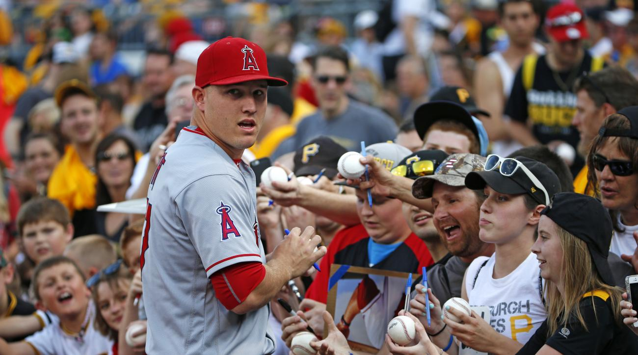 Los Angeles Angels' Mike Trout, left, signs autographs for fans before a baseball game against the Pittsburgh Pirates at PNC Park in Pittsburgh, Friday, June 3, 2016. (AP Photo/Gene J. Puskar)