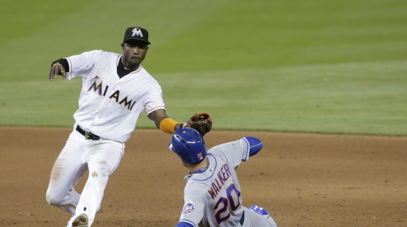 New York Mets' Neil Walker (20) is caught stealing second base by Miami Marlins shortstop Adeiny Hechavarria during the sixth inning of a baseball game, Friday, June 3, 2016, in Miami. (AP Photo/Wilfredo Lee)
