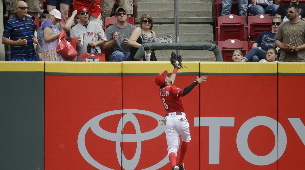 Cincinnati Reds center fielder Billy Hamilton (6) makes a leaping catch at the wall to put out Washington Nationals' Ben Revere in the first inning of a baseball game, Saturday, June 4, 2016, in Cincinnati. (AP Photo/John Minchillo)