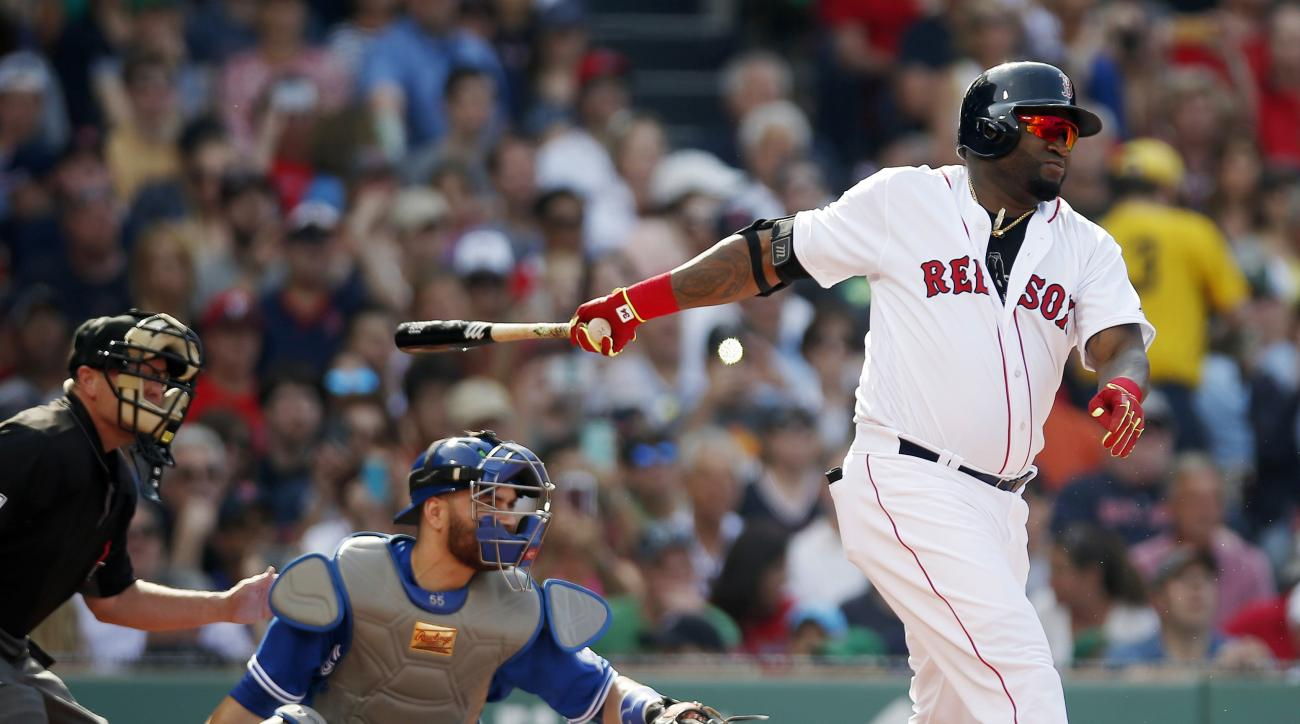 Boston Red Sox's David Ortiz, right, follows through on a two-run single in front of Toronto Blue Jays' Russell Martin during the third inning of a baseball game Saturday, June 4, 2016, in Boston. (AP Photo/Michael Dwyer)