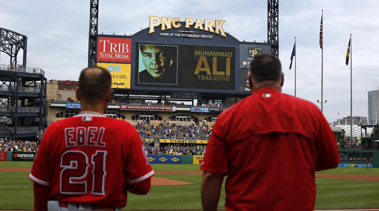 Los Angeles Angels manager Mike Scioscia, right, and bench coach Dino Ebel (21) pause for a moment of silence at PNC Park in memory of Muhammad Ali before a baseball game against the Pittsburgh Pirates in Pittsburgh, Saturday, June 4, 2016. (AP Photo/Gene