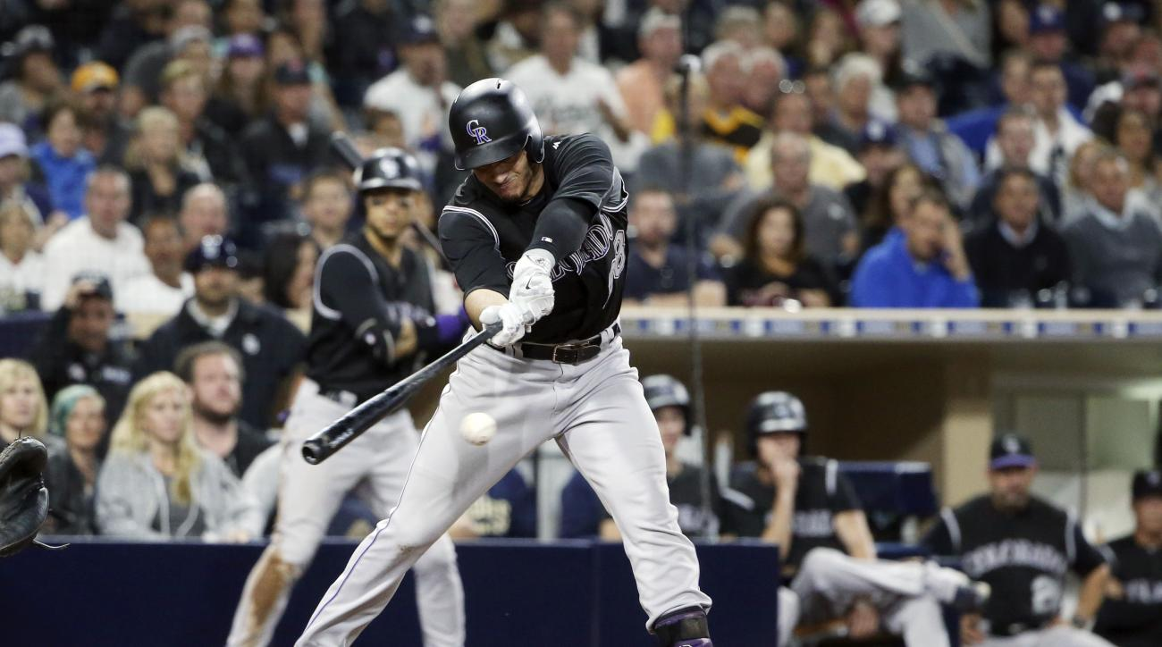 Colorado Rockies' Nolan Arenado reaches to slap a ground ball to first with bases loaded and two out in the sixth inning of a baseball game against the San Diego Padres, Saturday June 4, 2016, in San Diego. (AP Photo/Lenny Ignelzi)