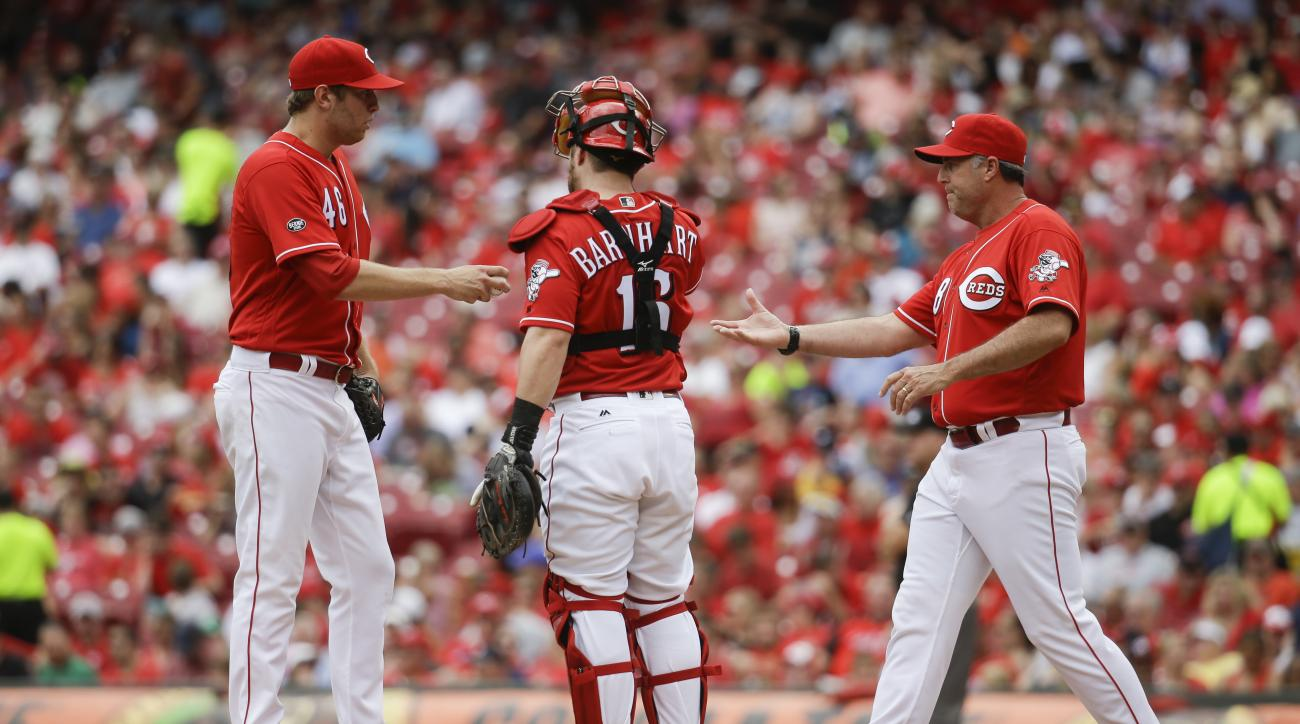 Cincinnati Reds starting pitcher Jon Moscot (46) hands the ball to manager Bryan Price, right, as he is relieved in the fourth inning of a baseball game against the Washington Nationals, Sunday, June 5, 2016, in Cincinnati. (AP Photo/John Minchillo)