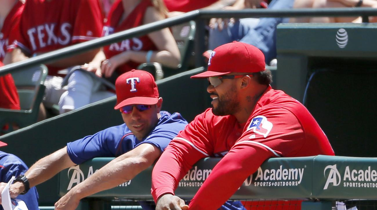 Texas Rangers field coordinator Jayce Tingler, left, talks with Prince Fielder, right, at the top of the dugout in the first inning of a baseball game against the Seattle Mariners on Sunday, June 5, 2016, in Arlington, Texas. (AP Photo/Tony Gutierrez)