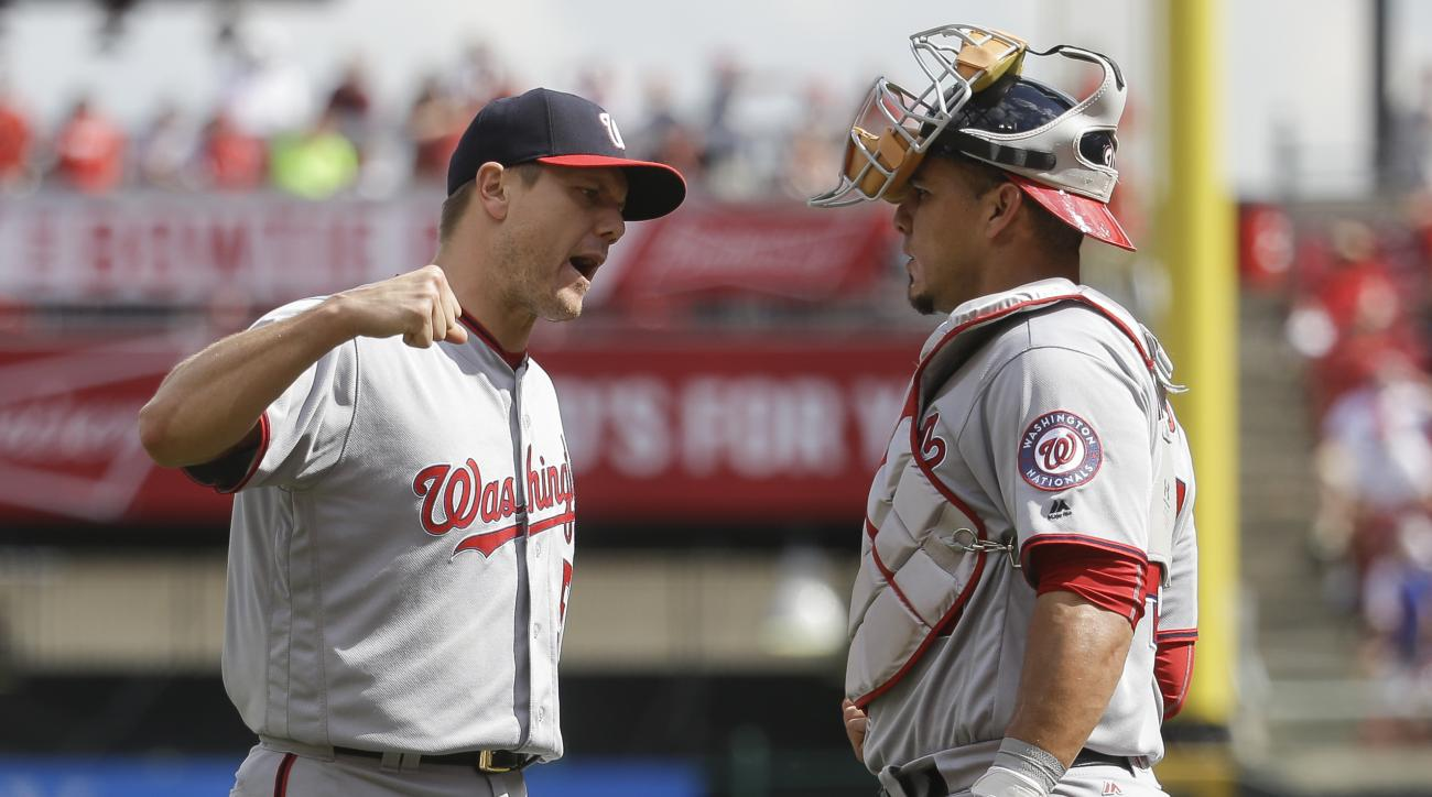 Washington Nationals relief pitcher Jonathan Papelbon, left, celebrates with catcher Wilson Ramos, right, after closing the ninth inning of a baseball game, Sunday, June 5, 2016, in Cincinnati. The Nationals won 10-9. (AP Photo/John Minchillo)
