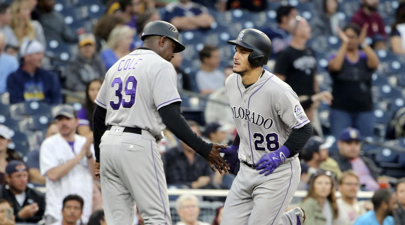 Colorado Rockies' Nolan Arenado is congratulated by third base coach Stu Cole after a home run in the fifth inning of a baseball game Sunday June 5, 2016, in San Diego. (AP Photo/Lenny Ignelzi)