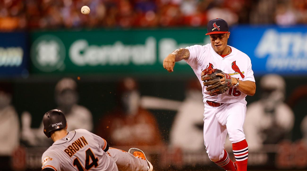 St. Louis Cardinals second baseman Kolten Wong, right, turns a double play over San Francisco Giants' Trevor Brown during the ninth inning of a baseball game Sunday, June 5, 2016 in St. Louis. (AP Photo/Scott Kane)