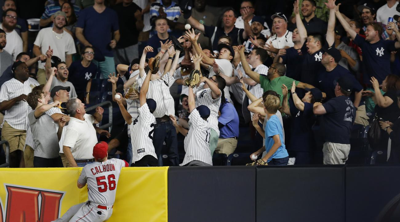 Los Angeles Angels right fielder Kole Calhoun (56) watches as fans scramble to catch Carlos Beltran's game-winning, eighth-inning, three-run, home run  ball during a baseball game at Yankee Stadium in New York, Monday, June 6, 2016. The Yankees defeated t