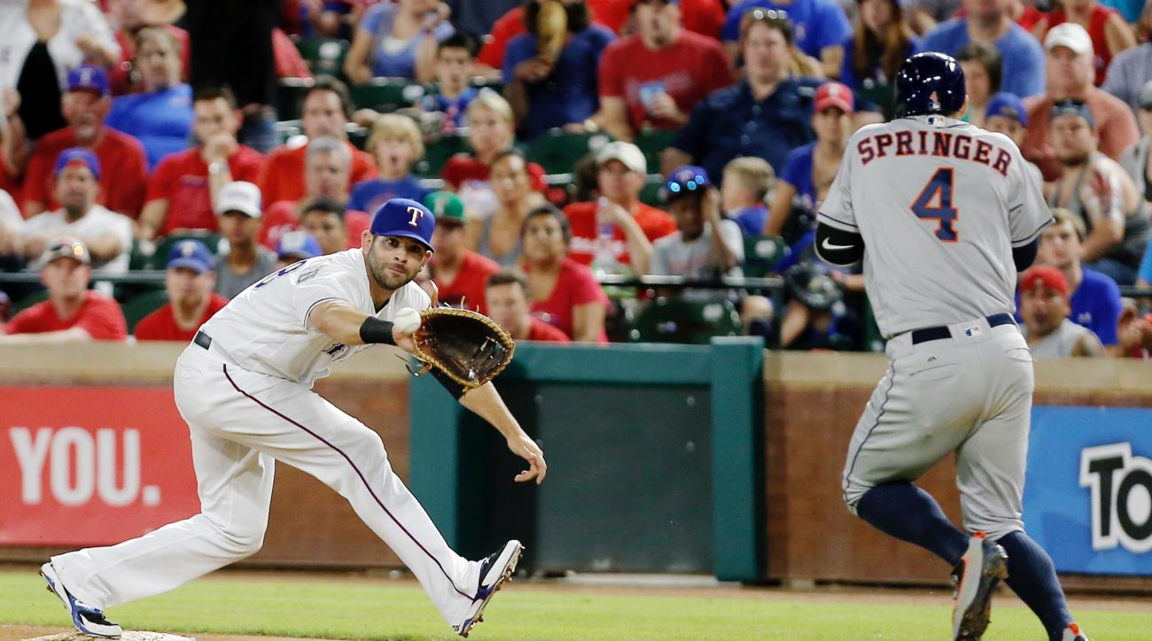 Texas Rangers first baseman Mitch Moreland, left, catches the throw from third to force out Houston Astros George Springer, right,  during the eighth inning of a baseball game Monday, June 6, 2016, in Arlington, Texas. (AP Photo/Brandon Wade)