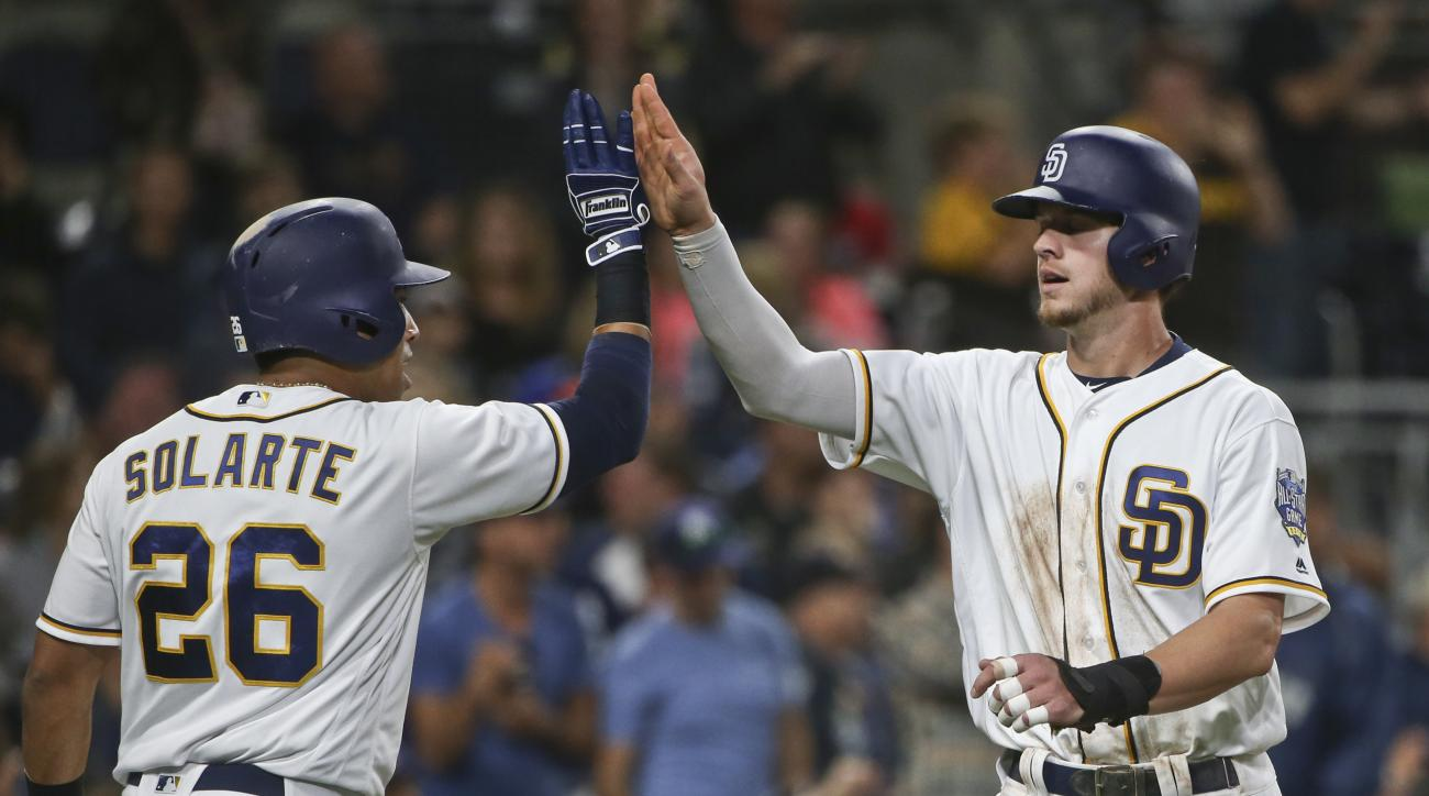 San Diego Padres' Wil Myers high fives with Yangervis Solarte after scoring on a double by Matt Kemp in the fifth inning of a baseball game Monday, June 6, 2016, in San Diego. (AP Photo/Lenny Ignelzi)
