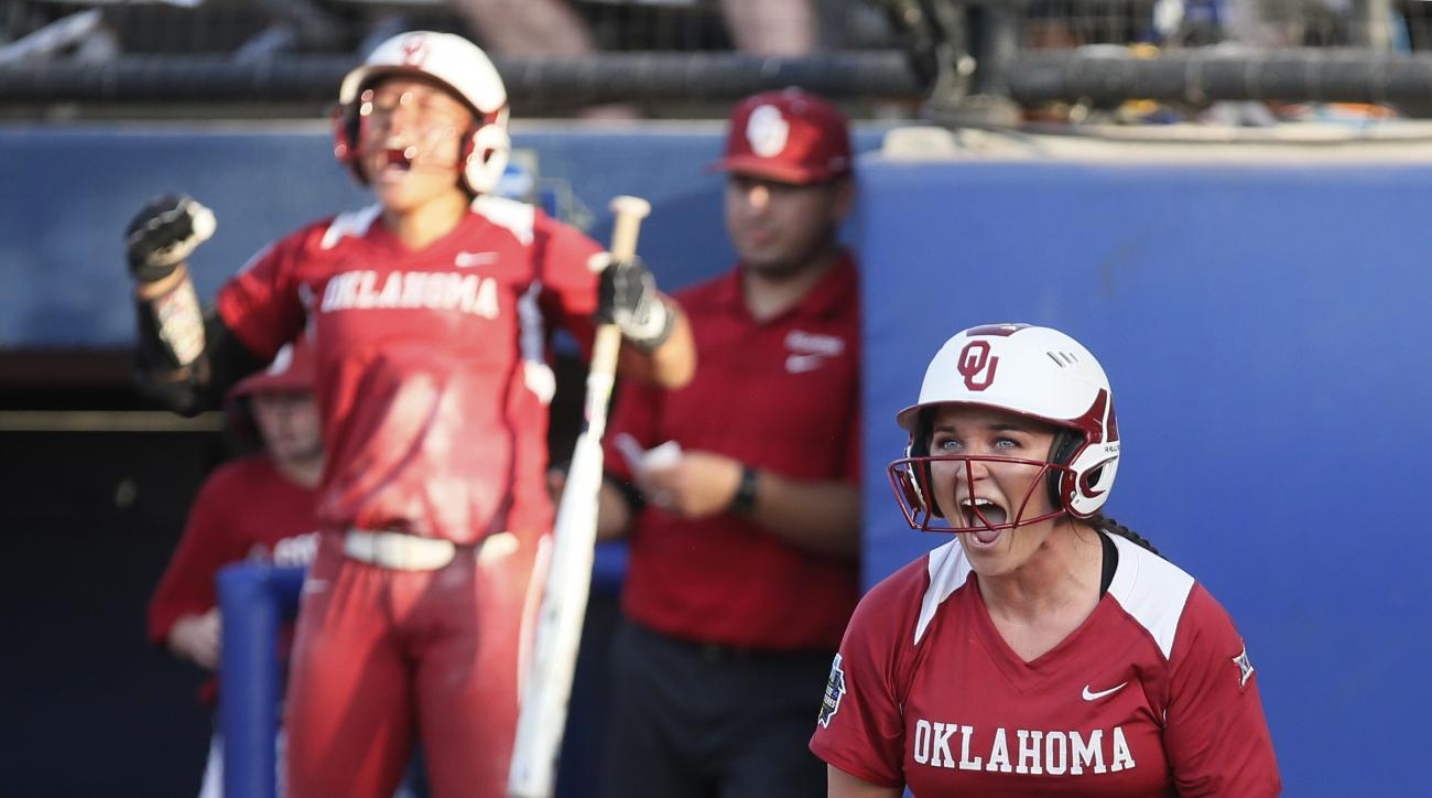 Oklahoma's Erin Miller, right, celebrates at home plate after scoring against Auburn during the second inning of the second game of the best-of-three championship series in the NCAA Women's College World Series in Oklahoma City, Tuesday, June 7, 2016. (AP