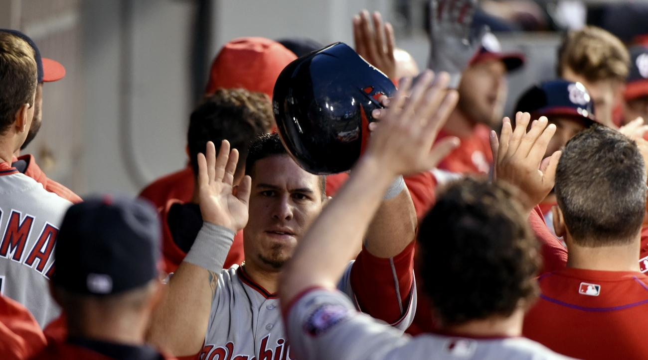 Washington Nationals Wilson Ramos, center, celebrates with teammates in the dugout after he scored on Anthony Rendon's two run homer against the Chicago White Sox during the fourth inning of a baseball game in Chicago on Tuesday, June 7, 2016. (AP Photo/M