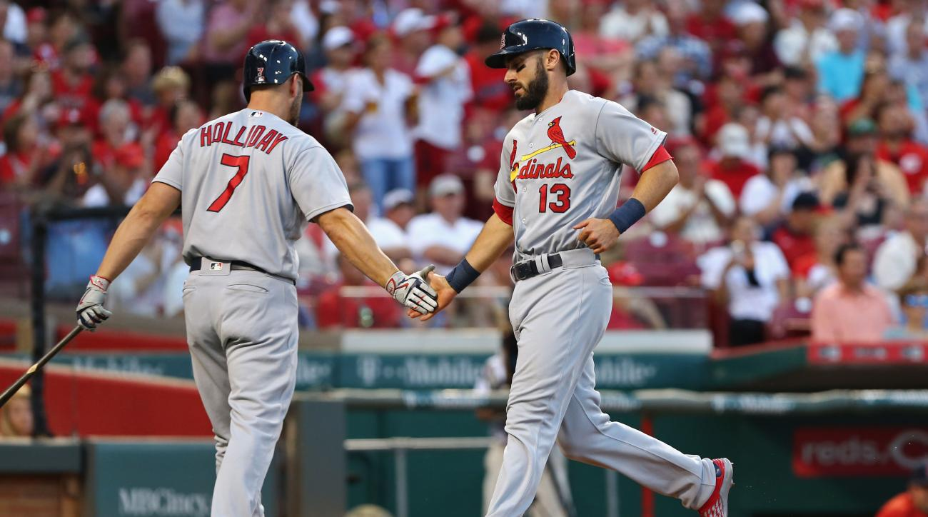 St. Louis Cardinals Matt Carpenter celebrates with left fielder Matt Holliday after scoring a run on an RBI single by Aledmys Diaz during the sixth inning of a baseball game, Thursday, June 9, 2016, in Cincinnati. (AP Photo/Aaron Doster)