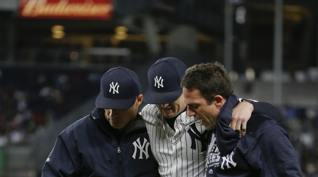 New York Yankees manager Joe Girardi, left, and assistant athletic trainer Tim Lentych help first baseman Chris Parmelee off the field during the seventh inning of a baseball game against the Los Angeles Angels on Thursday, June 9, 2016, in New York. (AP
