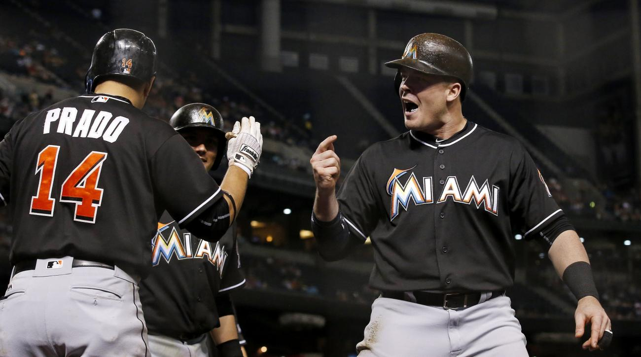 Miami Marlins' Justin Bour, right, celebrates his grand slam against the Arizona Diamondbacks with Martin Prado (14) and Miguel Rojas, rear, during the seventh inning of a baseball game Friday, June 10, 2016, in Phoenix. (AP Photo/Ross D. Franklin)