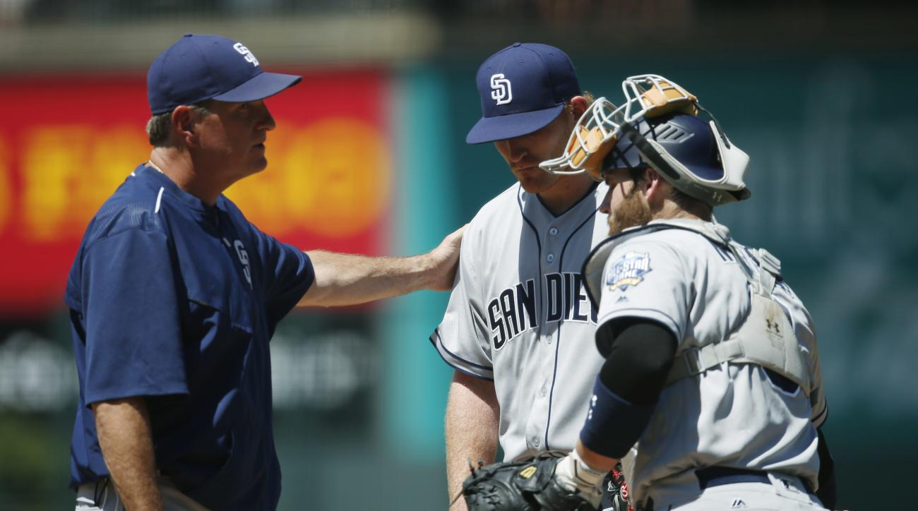 San Diego Padres pitching coach Darren Balsley, left, confers with starting pitcher Erik Johnson as catcher Derek Norris looks on as Johnson struggles against the Colorado Rockies in the first inning of a baseball game Saturday, June 11, 2016, in Denver.