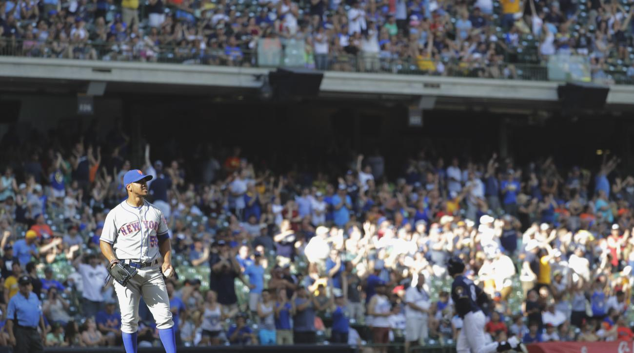 New York Mets relief pitcher Antonio Bastardo pauses as Milwaukee Brewers' Ryan Braun rounds the bases after hitting a home run during the seventh inning of a baseball game Saturday, June 11, 2016, in Milwaukee. (AP Photo/Morry Gash)