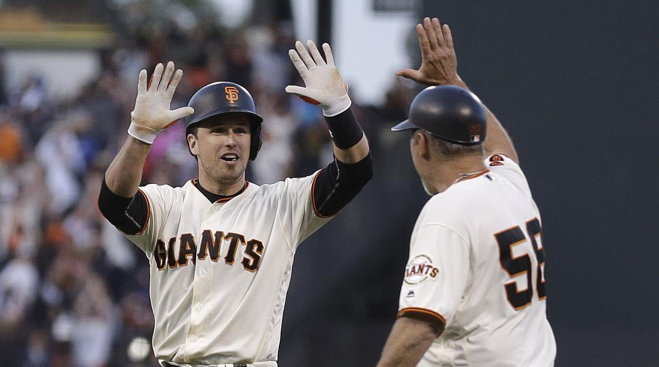 San Francisco Giants' Buster Posey, left, celebrates with first base coach Bill Hayes (58) after making the game winning hit against the Los Angeles Dodgers in the tenth inning of a baseball game, Saturday, June 11, 2016, in San Francisco. The Giants won