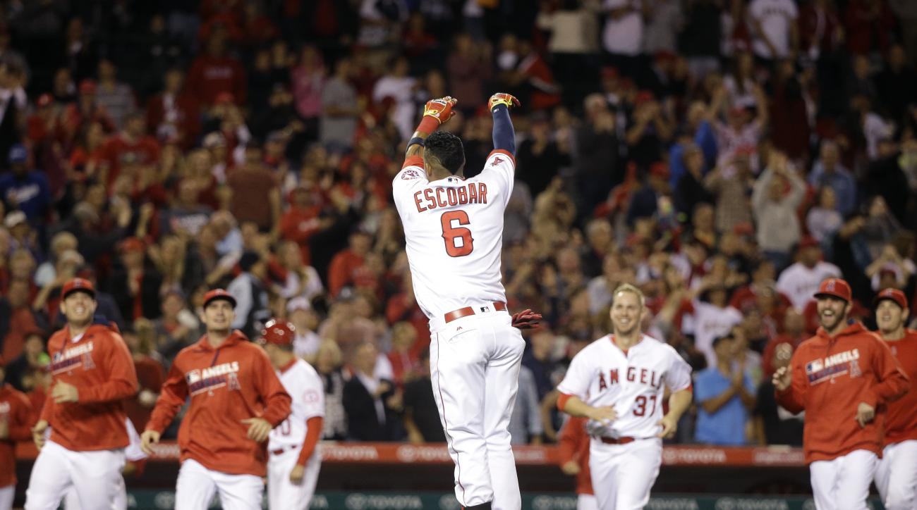 Los Angeles Angels' Yunel Escobar, center, tosses his helmet as he celebrates his ninth-inning walk-off single in a baseball game against the Cleveland Indians, Saturday, June 11, 2016, in Anaheim, Calif. The Angels won 4-3. (AP Photo/Jae C. Hong)