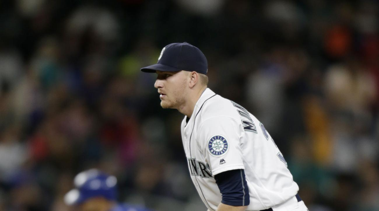 Seattle Mariners relief pitcher Mike Montgomery drops a rosin bag on the mound after giving up a solo home run to Texas Rangers' Rougned Odor, rear, during the 11th inning of a baseball game Saturday, June 11, 2016, in Seattle. The Rangers won 2-1. (AP Ph