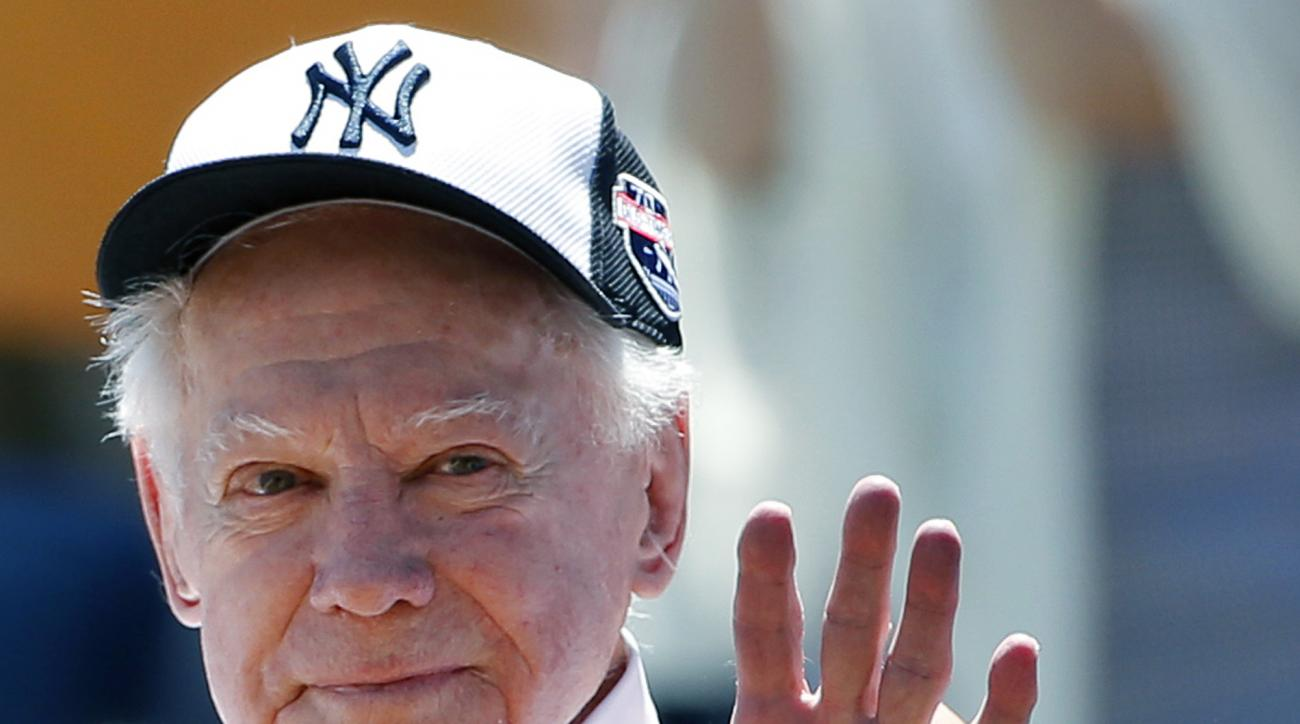 Former New York Yankees pitcher Whitey Ford waves to fans from outside the dugout at the Yankees' annual Old Timers Day baseball game, Sunday, June 12, 2016, in New York. (AP Photo/Kathy Willens)