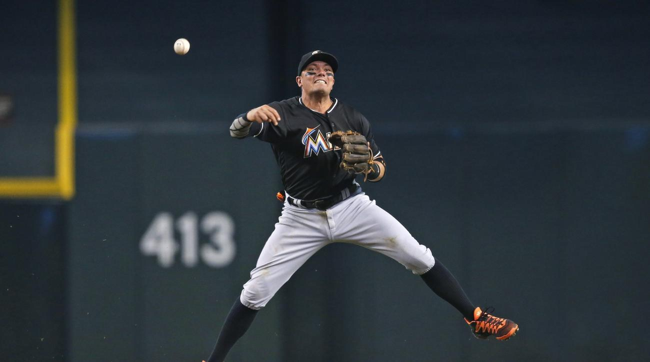 Miami Marlins' Miguel Rojas gets off a throw to first base in a vain attempt to get Arizona Diamondbacks' Nick Ahmed out during the first inning of a baseball game Sunday, June 12, 2016, in Phoenix. (AP Photo/Ross D. Franklin)