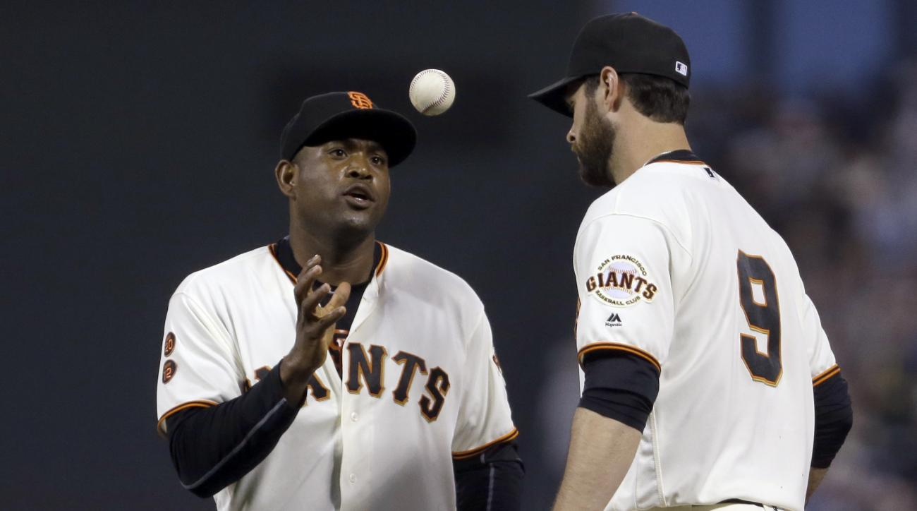 San Francisco Giants' Brandon Belt, right, flips the game ball to pitcher Santiago Casilla after the 2-1 win over the Los Angeles Dodgers at the end of a baseball game Sunday, June 12, 2016, in San Francisco. The Giants won 2-1. (AP Photo/Ben Margot)