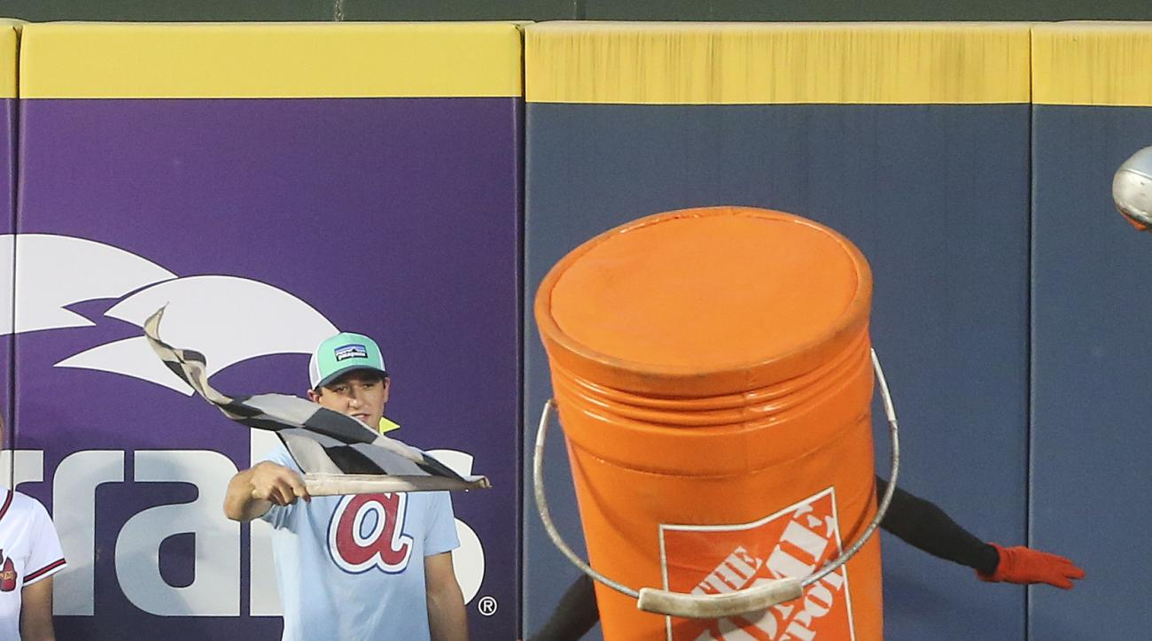 NASCAR driver Chase Elliott waves the checkered flag as Phil the Bucket crosses the finish line during the Home Depot Tool Race during the fifth inning of a baseball game between the Cincinnati Reds and the Atlanta Braves on Monday, June 13, 2016, in Atla