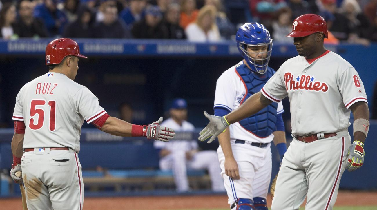 Philadelphia Phillies' Ryan Howard, right, is congratulated by teammate Carlos Ruiz after hitting a solo home run, as Toronto Blue Jays catcher Josh Thole watches during the seventh inning of a baseball game Monday, June 13, 2016, in Toronto. (Chris Young